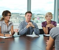 Panel of business people sitting at table in meeting room conduc